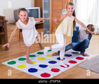 Two cheerful little sisters and teenage boy playing twister at home - Stock Photo