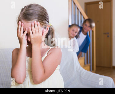 Teenage boy with little sisters playing hide-and-go-seek in home - Stock Photo