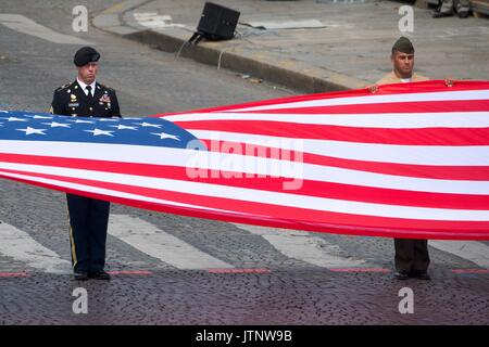 U.S. soldiers and Marines hold the American flag on the Champs Élysées during the annual Bastille Day military parade - Stock Photo
