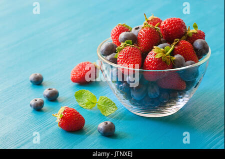 Berries in a glass plate on a blue wooden background. top view of Strawberry and blueberry in glass bowl on round - Stock Photo