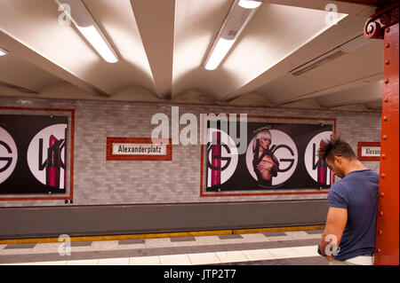 A lone passenger waiting for a train on the platform of Alexanderplatz U-Bahn station, Berlin, Germany - Stock Photo
