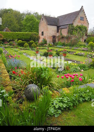 Portrait view of the Pavilion gallery at Chenies Manor sunken garden in spring, colourful tulips, variety of fresh - Stock Photo