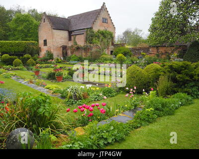 Chenies Manor sunken garden. Wet afternoon at tulip time; ornamental pond, apple tree, fresh greenery and plant - Stock Photo