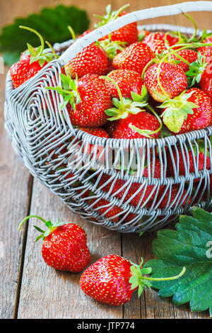Juicy fresh strawberries in a basket on wooden background, selective focus. - Stock Photo