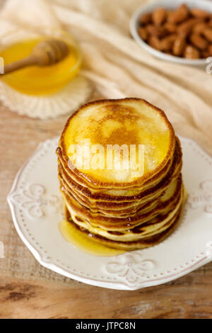 Homemade pancakes with honey and nuts, breakfast. - Stock Photo
