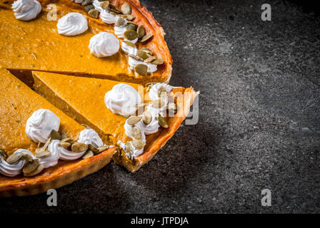 Traditional autumn dishes. Halloween, Thanksgiving. Sliced spicy pumpkin pie with whipped cream & pumpkin seeds - Stock Photo