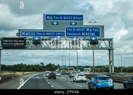 Blue sign on the M6 motorway, east of Birmingham, for the south west or north west of England, UK. - Stock Photo