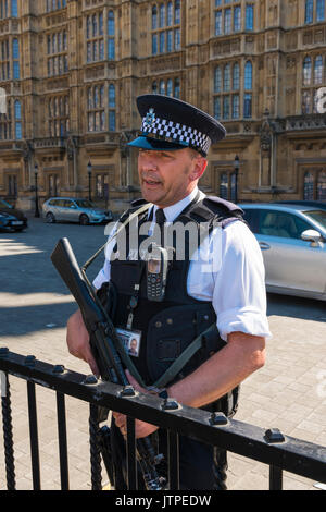 UK London Westminster Palace of Westminster Houses of Parliament Old Palace Yard armed policeman police officer - Stock Photo