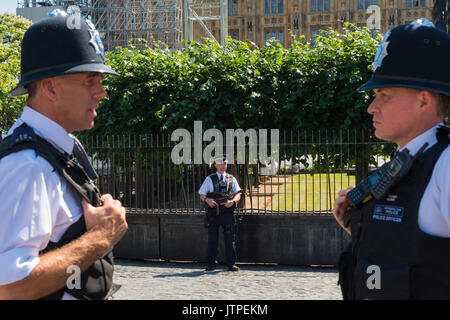 UK London Westminster Palace of Westminster Houses of Parliament security armed policeman policemen cops uniform - Stock Photo