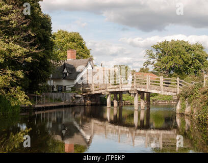 bridge crossing a river with reflections outside in country child and man on bridge; UK - Stock Photo