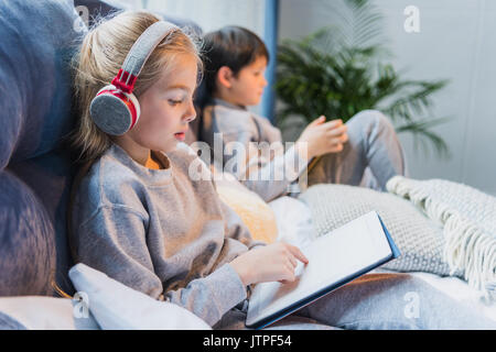 side view of focused girl in headphones and little boy using digital tablets - Stock Photo