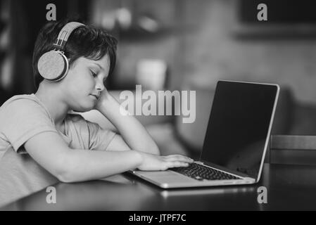 kid boy listening music in headphones while sitting at home and typing on laptop, black and white - Stock Photo