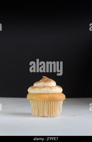 Cup cake background with single cupcake on white topped with cinnamon custard on rustic white with defocused black - Stock Photo