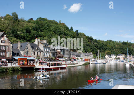 France. Brittany. Dinan. Harbourside houses and restaurants by River Rance with tourists in canoe and motor boat. - Stock Photo