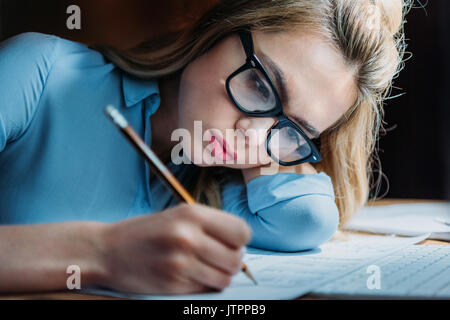 tired blonde caucasian student in eyeglasses lying on hand and writing something with pencil, studying till late - Stock Photo