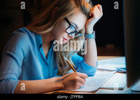 young blonde caucasian businesswoman in eyeglasses writing something with pencil and working till late - Stock Photo