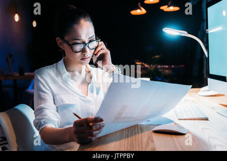 Young asian businesswoman in eyeglasses holding blueprint and talking on smartphone  - Stock Photo