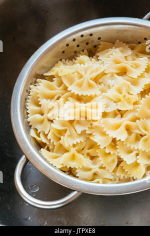 Cooked farfalle (bow-tie) pasta in a colander - Stock Photo