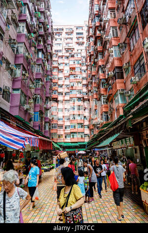 HONG KONG, JULY 6, 2017: A crowd of morning shoppers at a street market beneath the crowded apartments in Hong Kong's - Stock Photo
