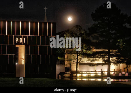 One gate at the Oklahoma City Memorial is lit up at night with a single silhouetted visitor and a full moon in the - Stock Photo