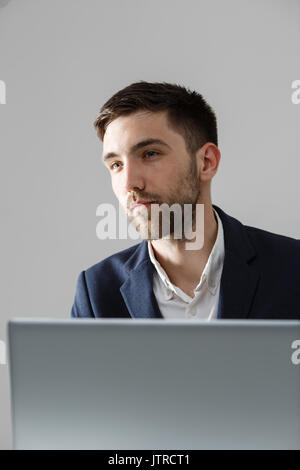 Business Concept - Portrait handsome stressful business man in suit shock looking at work in laptop. White Background. - Stock Photo