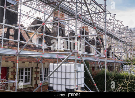 Scaffolding covering fire damaged houses, undergoing renovation - Stock Photo