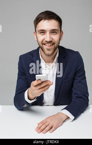 Business Concept - Portrait handsome happy handsome business man in suit playing moblie phone and smiling with laptop - Stock Photo