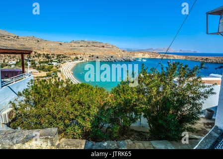 Small bay at Lindos on the island of Rhodes Greece crowded with beach umbrellas as boats and swimmers enjoy the - Stock Photo