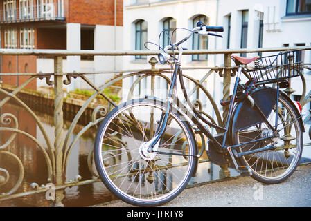 vintage bicycle parked against iron handrail on a bridge across a channel in Hamburg, Germany - Stock Photo
