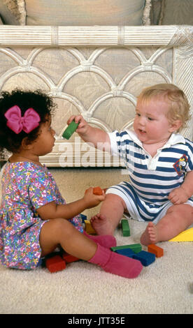 young caucasian baby sharing gives toy block to African American 2 year old girl 18 month old boy © Myrleen Pearson - Stock Photo