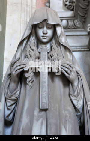 Mourning woman holding the cross depicted on the marble funeral monument to the Poggi Family by Italian sculptor - Stock Photo