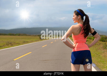asian chinese road runner standing on the asphalt street ready for training workout fit long running in the afternoon - Stock Photo