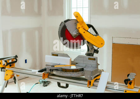 Carpenter cutting wooden plank with circular saw wearing safety equipment - Stock Photo