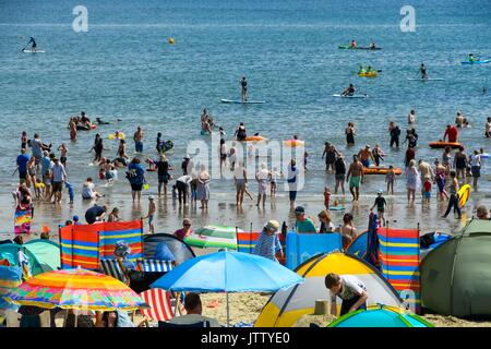 Lyme Regis, Dorset, UK. 10th August 2017.  UK Weather.   Holidaymakers and sunbathers pack the beach and cool off - Stock Photo