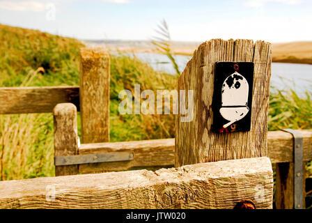 An acorn sign on a gate, denoting the South West Coast Path which runs beside the Fleet Lagoon - Stock Photo