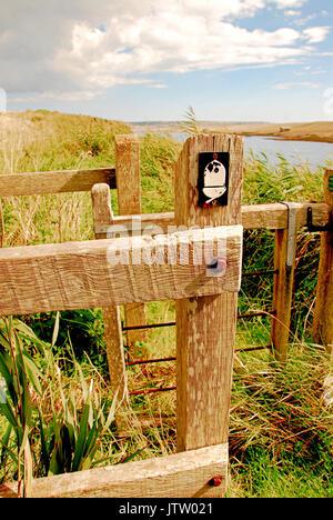An acorn sign on a 'kissing gate', denoting the South West Coast Path which runs beside the Fleet Lagoon - Stock Photo