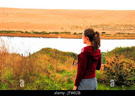 A young woman looks out from Weymouth, over the Fleet Lagoon to Chesil Beach beyond - Stock Photo