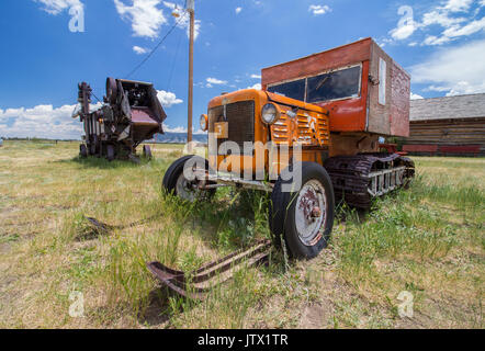 A snowmobile from a bygone age, complete with tracks and skis, rests on the prairie in the American west. - Stock Photo