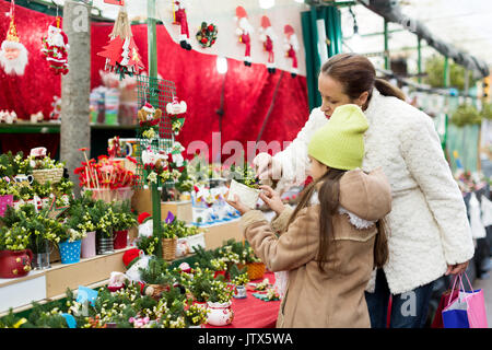 girl with mother choosing mistletoe decorations for Christmas. Focus on woman - Stock Photo