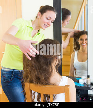 Happy smiling young woman brushing her friend in front of the mirror at home - Stock Photo