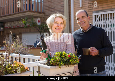 Positive smiling elderly woman with horticultural sundry and aged man drinking tea in patio - Stock Photo