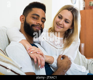 Happy spouses sitting on sofa, hugging and smiling indoors - Stock Photo