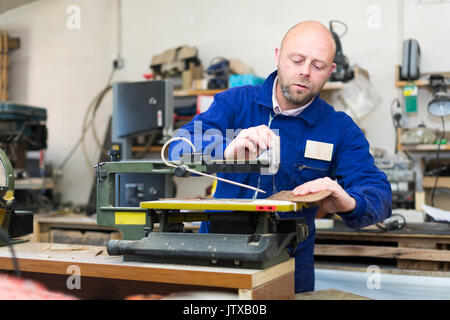 Portrait of professional woodworker working on a lather in a workshop - Stock Photo