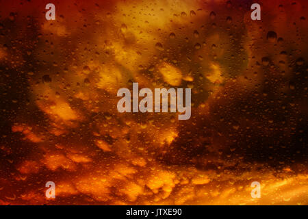 Looking through a misty window with raindrops at the dramatic storm clouds brewing at sunset - Stock Photo