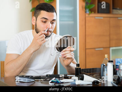 Guy 20 years old remove hair from his nose and ears with trimmer - Stock Photo
