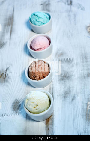 Selection of gourmet flavours of Italian ice cream in vibrant colors served in individual porcelain cups on an old - Stock Photo