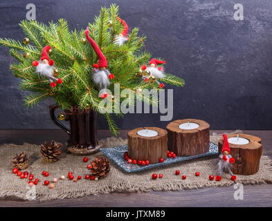 Christmas Composition with Gifts and Burning Candle. Basket, red balls, pine cones, snowflakes on Grey Background. - Stock Photo