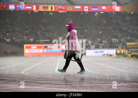 An official walking across the running track in pouring rain at the World Para Athletics Championships London Stadium - Stock Photo