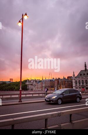 London, England - July 26, 2017 :  Private black car driving on the Blackfriars Bridge at dusk, London, England - Stock Photo