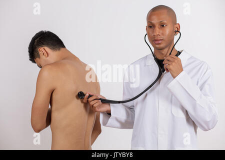 Auscultating procedure, Male doctor auscultating a young male patient by using a stethoscope - Stock Photo